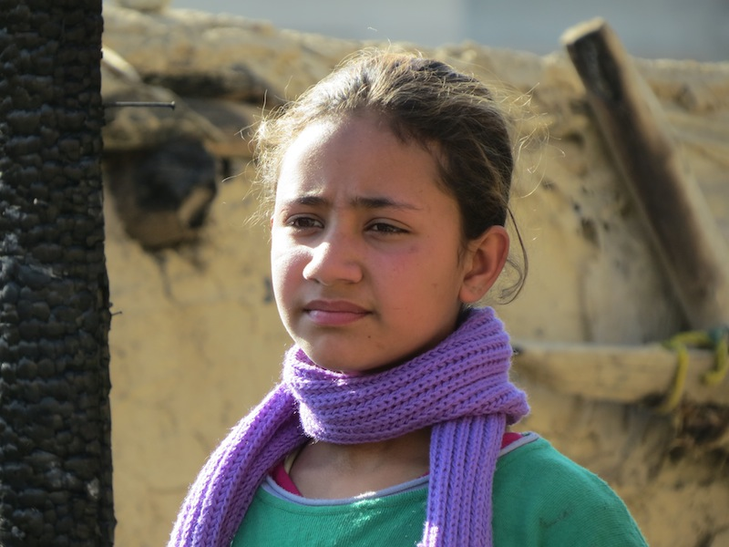 Girl standing where her home burned to the ground