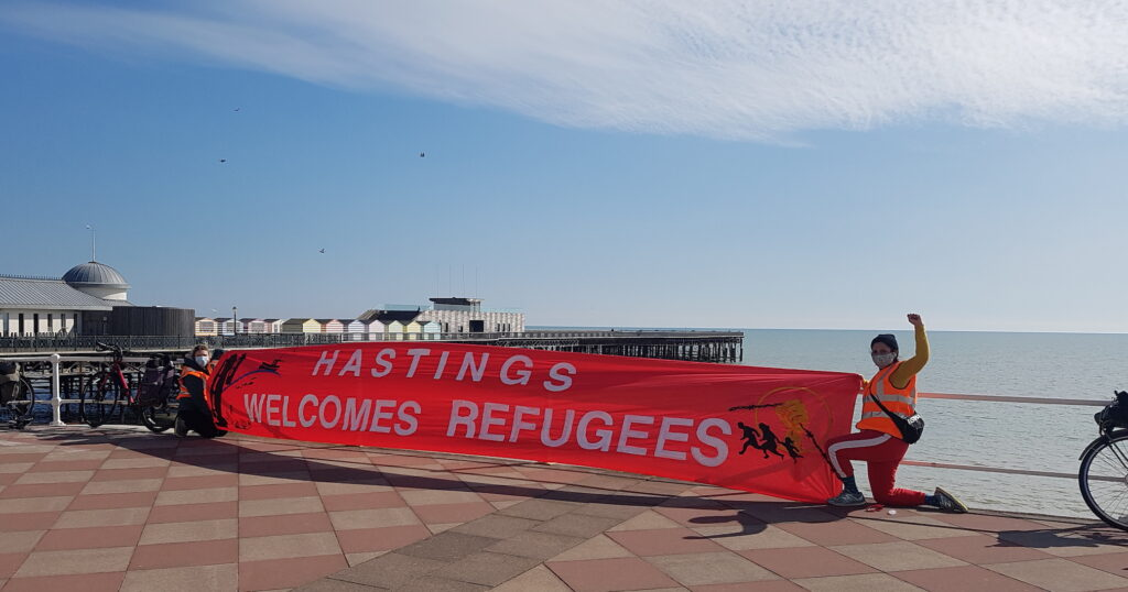 Maya Evans on the seafront in Hastings. She is wearing sports clothes, kneeling on one knee, raising her left fist and holding a banner saying, 'Hastings welcomes refugees'